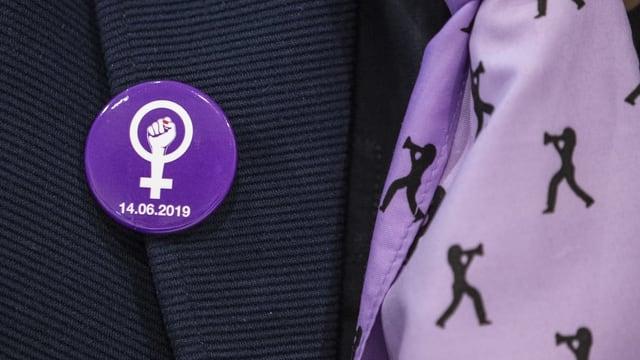 Violetter Button mit gereckter Faust und dem Zeichen für das weibliche Geschlecht.