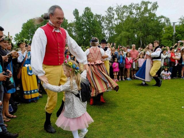 Ein Mann in einer Tragt tanzt  mit einem Mädchen auf einer Wiese. Viele Leute schauen zu.
