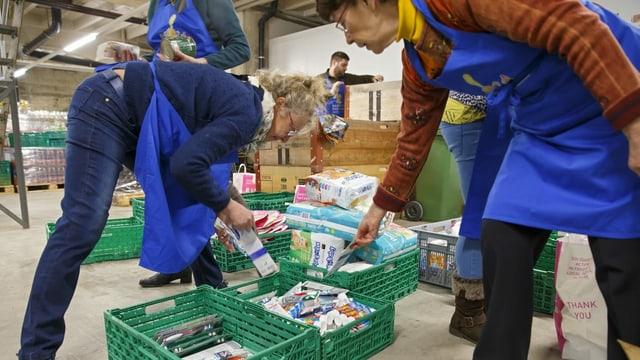 Frauen in Schürzen füllen Harassen mit Lebensmitteln