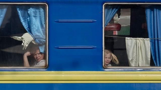 Ein Zug mit den Landesfarben der Ukraine. Zwei Passagiere schauen aus dem Fenster.