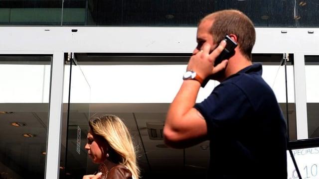 Ein Mann geht hinter einer Frau an einem Gebäude vorbei und telefoniert.