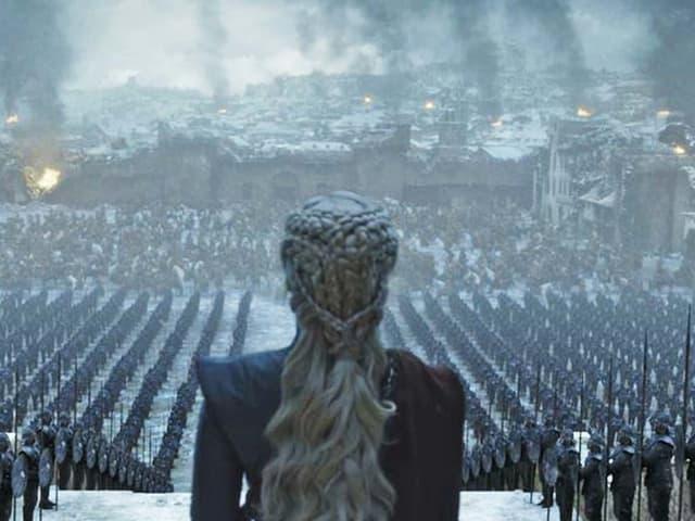 Eine Frau steht vor einer brennenden Stadt.