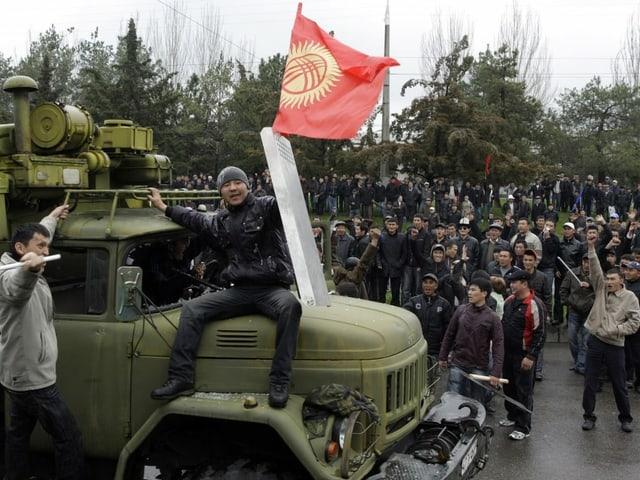 Eine Menschenmenge umringt ein Militärfahrzeug. Ein Mann hat sich auf die Motorhaube gesetzt, in seiner Hand ein Polizeischild und die Nationalflagge. Bild von 2005.