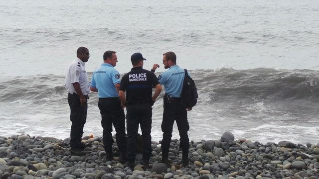 Vier Polizisten stehen an einem Strand von La Réunion