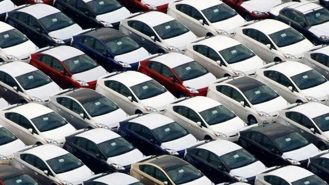 Viele Toyotas auf einem Parkplatz.