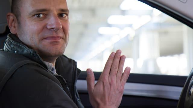 Digitalredaktor Reto Widmer im autonomen BMW, die Hände weg vom Lenkrad, in betender Pose.