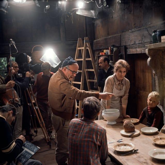 Zwei der Kummerbuben sitzen am Esstisch, die Mutter steht am Kopf des Tisches auf ihre Hände abgestützt. Franz Schnyder steht auch am Tisch und gibt den beiden Jungs Regieanweisungen.