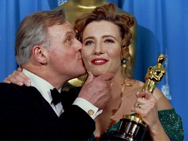 Anthony Hopkins (links) küsst Emma Thompson auf die Wange, die eine Oscartrophäe in der Hand hält