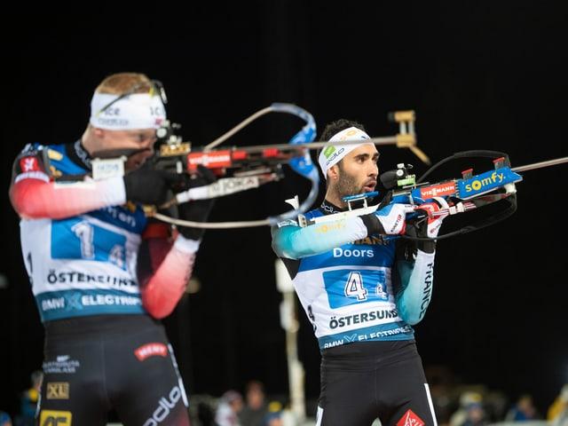 Martin Fourcade (r.) und Johannes Thingnes Bö am Schiesstand.
