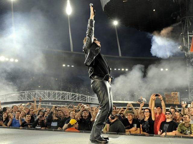 Mann auf Bühne vor Publikum streckt Arm in die Luft
