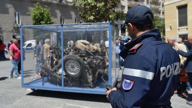 Autowrack in einem Glaskäfig, daneben steht ein Polizist.