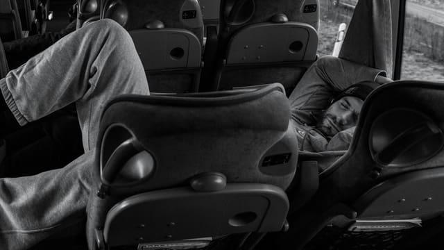 Ein Mann liegt in einem Mannschafts-Bus und schläft.