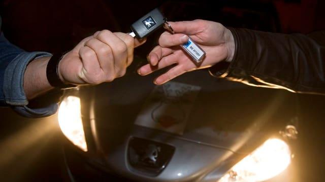 Zwei Hände tauschen zwei Autoschlüssel