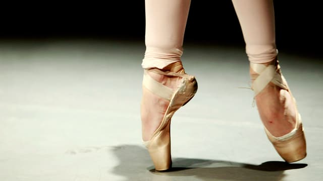 Die Füsse einer Ballerina in Spitzenschuhen.