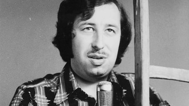 Schwarzweiss-Aufnahme des jungen Roland Jeanneret mit Mikrofon.