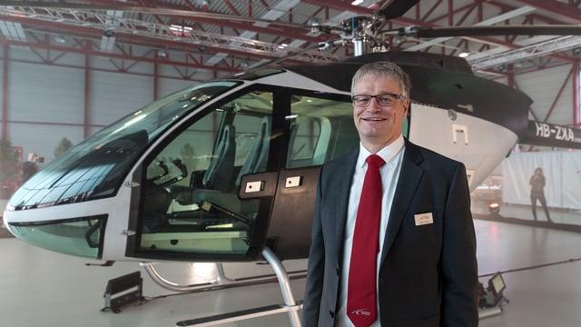 Martin Stucki steht vor einem Helikopter.