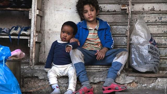 Zwei Kinder sitzen auf einer Treppe.