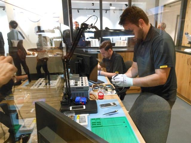 Ein Mann mit dunklem T-Shirt und weissen Handschuhen untersucht ein Smartphone.