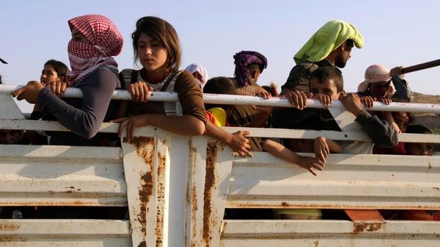 Jesidische Frauen und Männer auf der Ladefläche eines Lastwagens auf der Flucht.