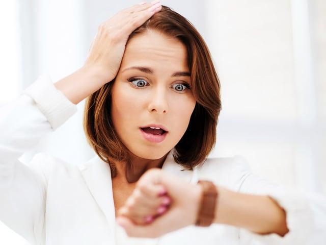 Frau schaut entsett auf ihre Armbanduhr und hält sich den Kopf