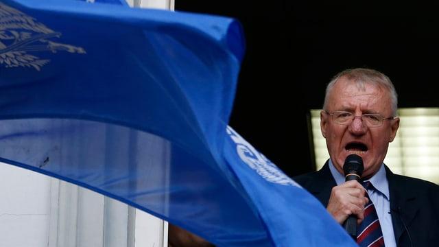 Seselj spricht in ein Mikrofon, eine blaue Flagge verdeckt ihn halb.