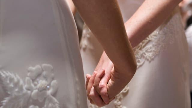 Zwei Frauen vor dem Traualtar halten sich die Hände