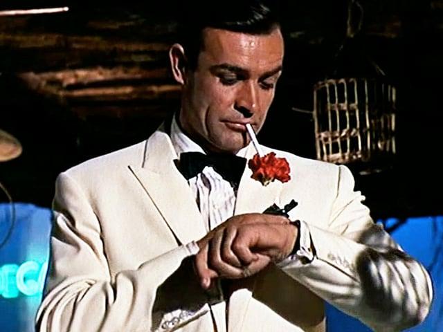 Bond im Anzug schaut auf seine Armbanduhr