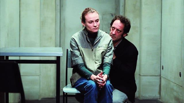 Eine Frau sitzt in einem tristen Raum auf einem Stuhl, ein Mann kniet neben ihr.