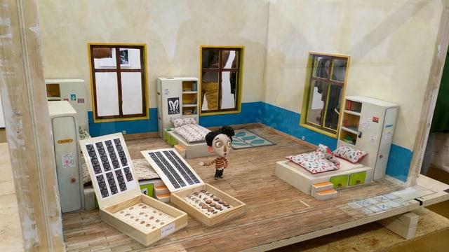 Eine Puppe in einer Art Puppenhaus, davor Boxen mit Puppen-Elementen