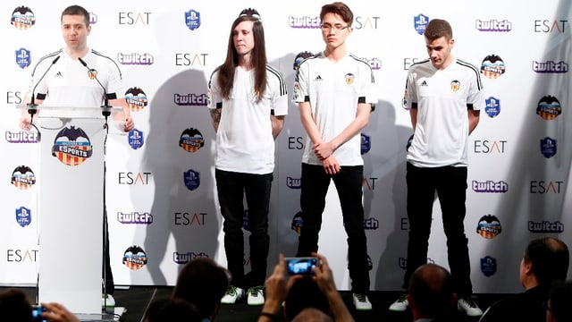 Ein Sprecher und drei junge Männer auf einer Bühne.
