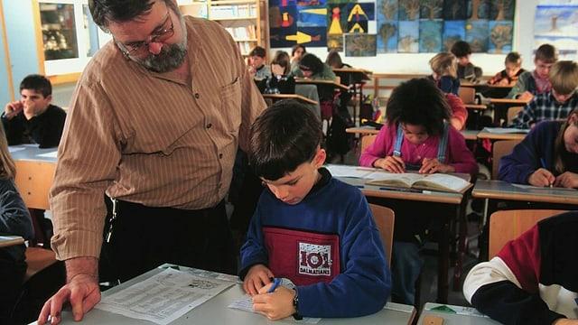 Lehrer erklärt Schüler eine Aufgabe.