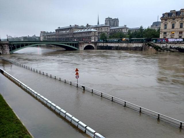 Überfluteter Weg neben einem Fluss. Im Hintergrund Brücke und Stadthäuser.