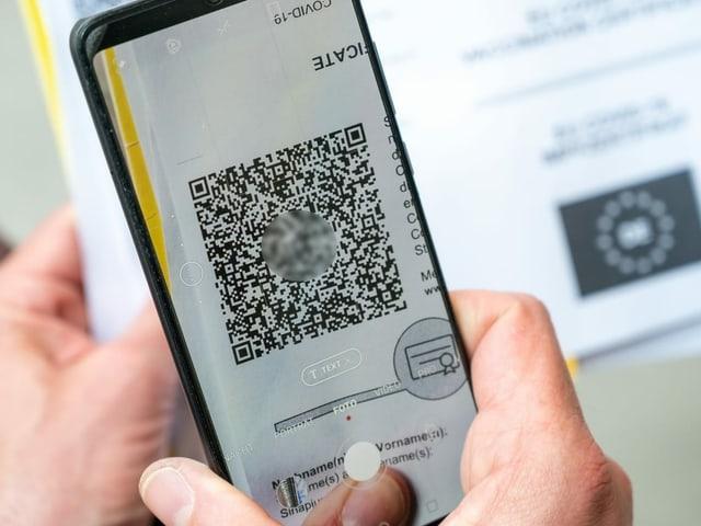 Handy scannt QR-Code für Impfausweis