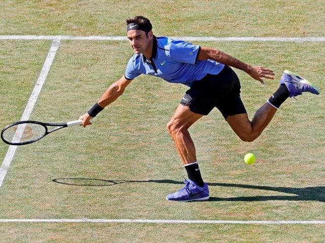 Roger Federer macht sich am Netz lang.