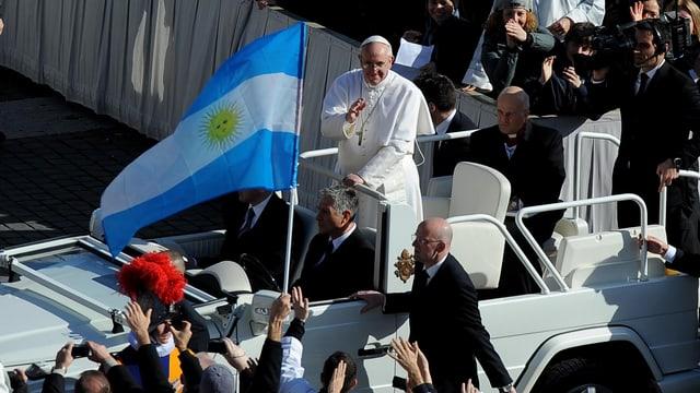 Papst Franziskus grüsst die Menge, eine argentinische Flagg im Vordergrund