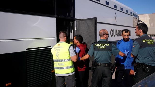 Migranten steigen in einen Bus