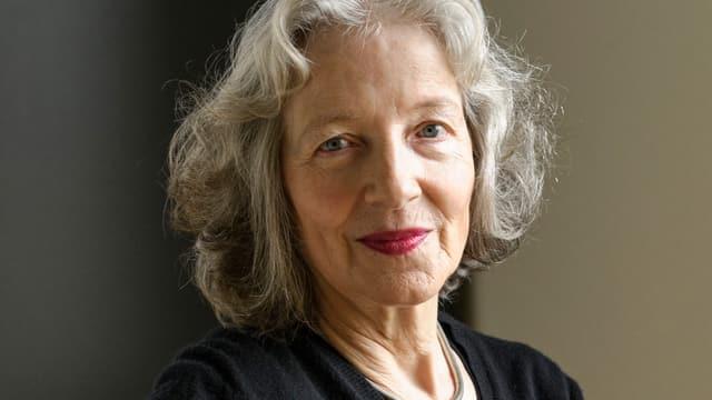 Porträtbild einer Frau mit halblangen grauen Haaren, halbnah