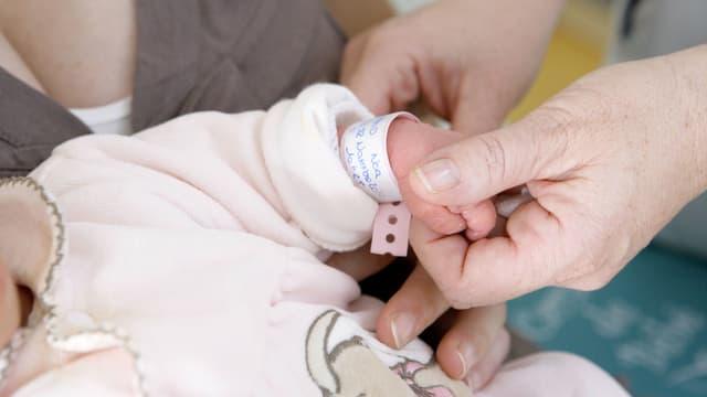 Eine Frau zieht einem Baby ein Band mit dem Namen an.
