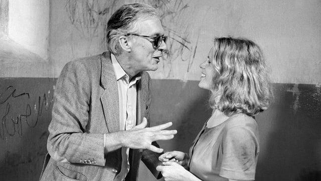 Ein Man im Jackett und Brille unterhält sich mit einer blonden Frau.