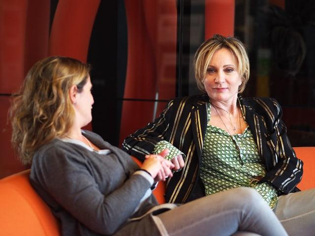 Patricia Kaas sitzt mit Riccarda Trepp auf einem orangen Sofa.
