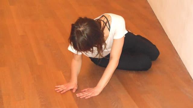 Eine Frau in Gymnastikhose und weissem T-Shirt sitzt leicht verdreht auf Holzboden.
