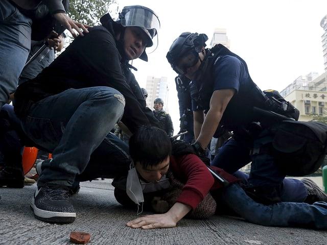 Zwei Polizisten in voller Montur drücken einen jungen Mann zu Boden.