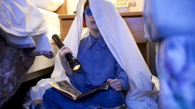 Ein Junge sitzt im Schneidersitz am Boden. Er trägt eine Schwimmbrille und hat ein Tuch über dem Kopf und liest mit einer Taschenlampe einen Comic.