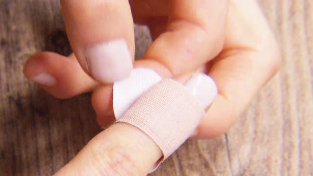 Eine Frau bringt ein Pflaster an ihren Zeigefinger an.