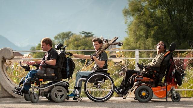 Filmszene: Drei junge Männer im Rollstuhl nitereinander, In der Mitte Joel Basman als Valentin mit einem grossen Kruzifix auf der Schulter