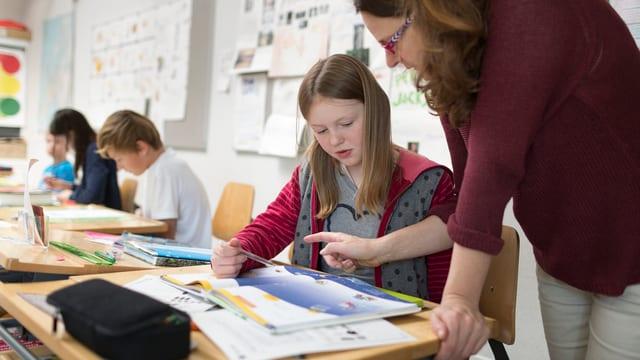 Eine Lehrerin erklärt einer Schülerin im Klassenzimmer eine Aufgabe,