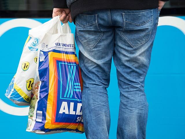 Ein Mann trägt volle Einkaufstaschen aus Deutschland