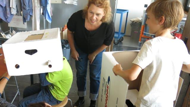 Zwei Kinder halten zwei grosse Schachteln. Sie sind daran, aus diesen Schachteln Zeitmaschinen zu bauen. Im Hintergrund steht die Gründerin Sabine Gysin, die sich die Maschinen erklären lässt.