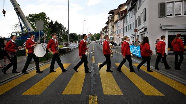 Musikanten überqueren einen Fussgängerstreifen in der Stadt Zug.