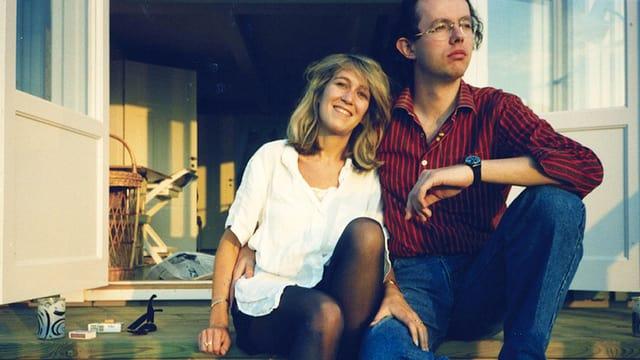 Eine blonde Frau sitzt mit einem Mann auf der Veranda.